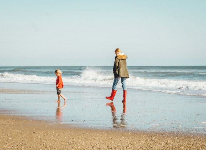 Mother walking with child on beach