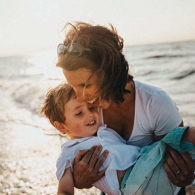 Mother holding son on beach